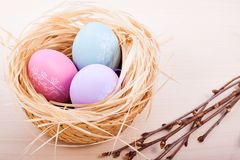 Easter eggs in nest on rustic wooden planks. Colored easter eggs in nest on rustic wooden planks with branch stock photo
