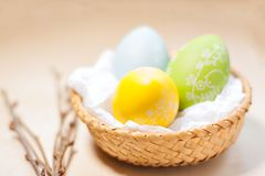 Easter eggs in nest on rustic wooden planks. Colored easter eggs in nest on rustic wooden planks with branch stock images