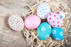 Easter eggs in nest on rustic wooden planks with copyspace. Happ Royalty Free Stock Images