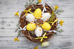 Easter eggs in nest on rustic wooden planks. With flowers Royalty Free Stock Image