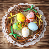 Easter eggs in nest on rustic wooden planks. With flowers Royalty Free Stock Photography