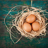 Easter eggs in nest on rustic wooden planks Royalty Free Stock Photo