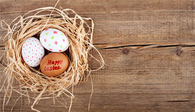 Easter eggs in nest on rustic wooden planks Stock Photos