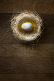 Easter eggs in nest on rustic wooden table Stock Photo