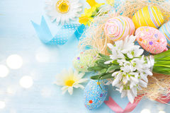 Easter eggs in the nest with spring flowers. Over wooden background Stock Photography