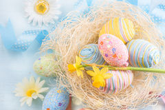 Easter eggs in the nest with spring flowers. Over wooden background Royalty Free Stock Image