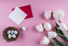 Easter eggs in nest and tulip flowers on spring background. Top view with copy space. Happy Easter card.  royalty free stock image