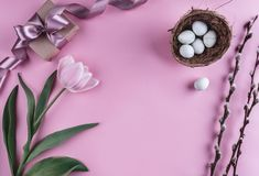 Easter eggs in nest and tulip flowers on spring background. Top view with copy space. Happy Easter card.  royalty free stock images
