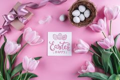 Easter eggs in nest and tulips flowers on pink background with Easter card. Waiting for spring. Top view with copy space stock photo