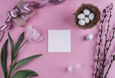 Easter eggs in nest and tulips flowers on spring background. Top view with copy space. Happy Easter card. Stock Photo