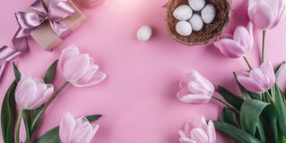 Easter eggs in nest and tulips flowers on spring background. Top view with copy space Stock Photo
