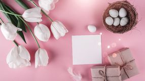 Easter eggs in nest and tulips flowers on spring background. Top view with copy space. Royalty Free Stock Photos