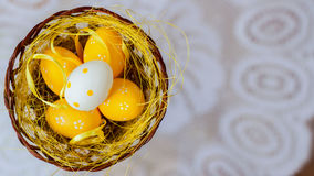 Easter eggs in a nest on a white background of white lace doily. Festive decorations. Top view. Place for your text. For Stock Photo