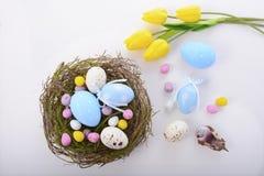 Easter eggs in nest on white wood table. Stock Image