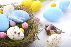 Easter eggs in nest on white wood table. Royalty Free Stock Photos