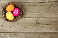 Easter eggs in nest on wood. Easter eggs in a nest over an old wood background stock image