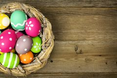 Easter eggs in nest on wood. Easter eggs in a nest over an old wood background royalty free stock image