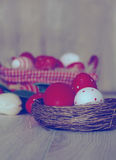 Easter eggs in nest on wooden background. Royalty Free Stock Image