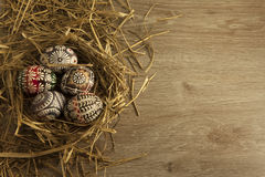 Easter eggs in nest on wooden background Stock Images