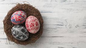 Easter eggs in the nest on wooden background. Pysanky in the nest on white wooden background. Easter eggs decorated with wax-resist dyeing technique, traditional Royalty Free Stock Image
