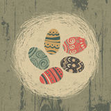 Easter eggs in nest on wooden texture. Stock Photos