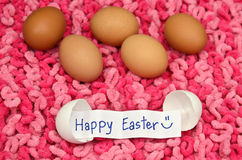 Easter eggs with note in shell on pink fabric background Stock Photography