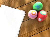 Easter eggs notebook. Colorful Easter eggs on a table next to notebook sheets Stock Image