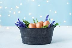 Easter eggs in an old bowl, grass, flowers on a blue background with bokeh. Easter and spring concept royalty free stock photography