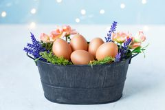 Easter eggs in an old bowl, grass, flowers on a blue background with bokeh. Easter and spring concept royalty free stock images