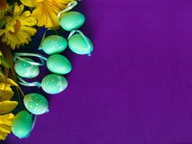 Easter Eggs On Purple Silk, With Yellow Flowers. Royalty Free Stock Images