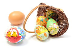 Easter eggs in overturned wicker basket Stock Photos