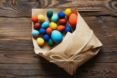 Easter eggs are packed in a paper bag as a gift on a wooden background stock images