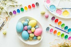 Easter eggs, paint and brushes. Holiday concept. Flat lay. Top view. stock photos