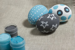 Easter eggs with paint jars. The traditional eggs ornamented by paints, shades blue and gray Royalty Free Stock Photography