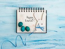 Easter eggs painted in bright colors on a blue background. Top view, close-up, isolated. Happy Easter. Preparation for the holiday stock photo