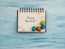 Easter eggs painted in bright colors, notebook page. On a blue background. Top view, close-up, isolated. Preparation for the holiday. Congratulations for loved stock photos