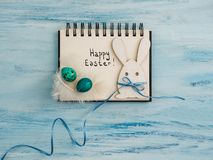 Easter eggs painted in bright colors, notebook page. On a blue background. Top view, close-up, isolated. Preparation for the holiday. Congratulations for loved royalty free stock photo