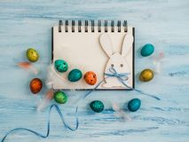 Easter eggs painted in bright colors, notebook page. On a blue background. Top view, close-up, isolated. Preparation for the holiday. Congratulations for loved stock images