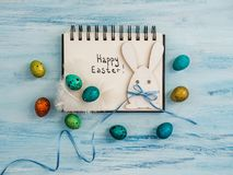 Easter eggs painted in bright colors, notebook page. On a blue background. Top view, close-up, isolated. Preparation for the holiday. Congratulations for loved stock image