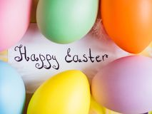 Easter eggs painted in bright colors on a yellow background. Top view, close-up, isolated. Happy Easter. Congratulations for loved ones, relatives, friends and stock image