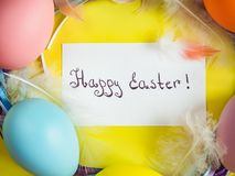 Easter eggs painted in bright colors on a yellow background. Top view, close-up, isolated. Happy Easter. Congratulations for loved ones, relatives, friends and royalty free stock photo