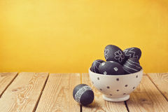 Easter eggs painted with chalkboard paint on wooden table Royalty Free Stock Photo