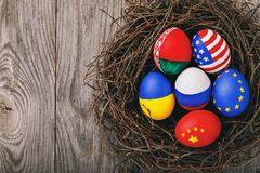 Easter eggs painted in the colors of flags different states of the world in the nest with copy space. View from above royalty free stock photos