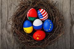 Easter eggs painted in the colors of the flags of different states of the world in the nest. View from above royalty free stock images