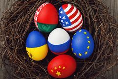 Easter eggs painted in colors of the flags of different states of the world in the nest. Top view stock photo