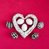 Easter eggs painted like zebra, cow, snow leopard. Three white eggs inside a white heart on red background. Top view. stock photography