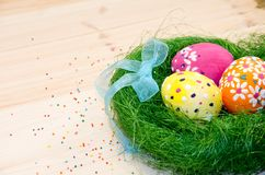 Easter eggs painted in a nest of grass with a bow. On wooden background Stock Images