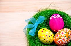 Easter eggs painted in a nest of grass with a bow. On wooden background Royalty Free Stock Photos