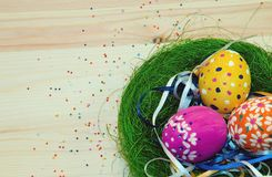 Easter eggs painted in a nest of grass with a bow. On wooden background Royalty Free Stock Photo