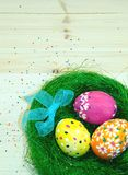 Easter eggs painted in a nest of grass with a bow. On wooden background Royalty Free Stock Images